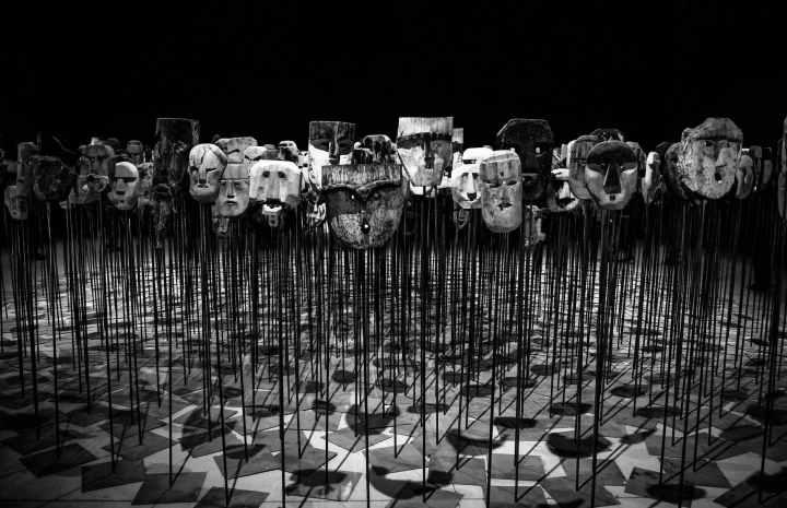 greyscale photo of masks on a stick